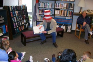 man with Cat In the Hat hat on reads a Dr. Seuss book to children