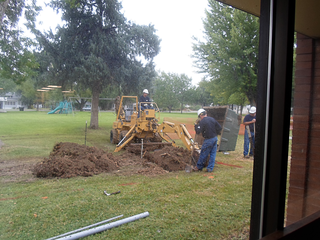 backhoe digging trench outside library