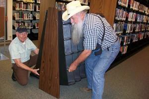 two men lift a display shelf