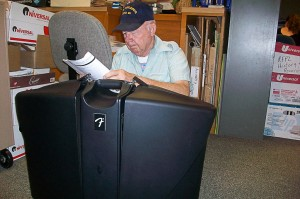 man sitting behind large black electronic equipment case, reading an instruction manual