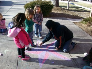 teacher draws colorful star with chalk on sidewalk while three children look on