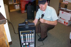 man holding microphone kneels next to portable amplifier