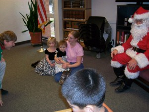 children and Santa Claus listening to story teller