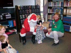 Santa Claus hugs child while parent and story teller laugh